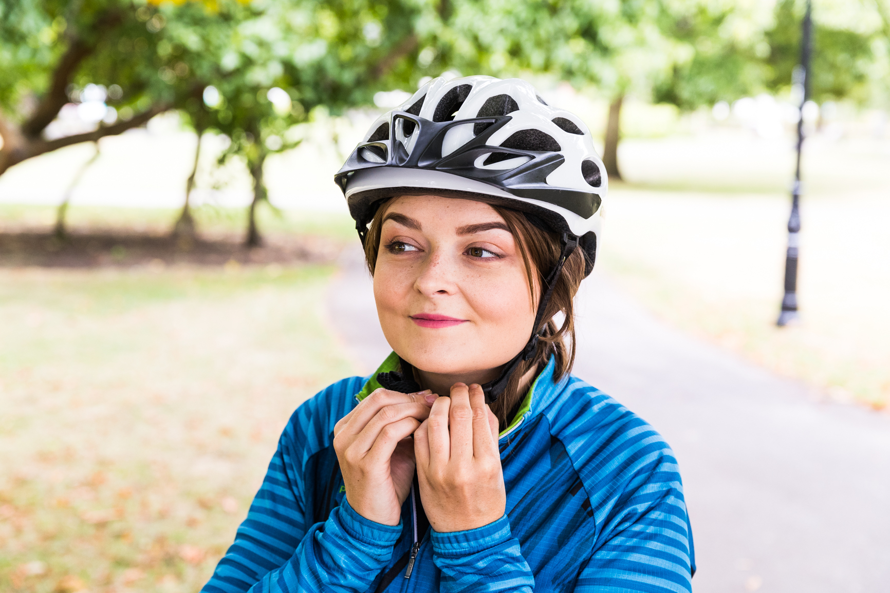 Woman cyclist clipping helmet